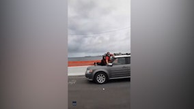 Man seen clinging to hood of moving car during Florida demonstrations