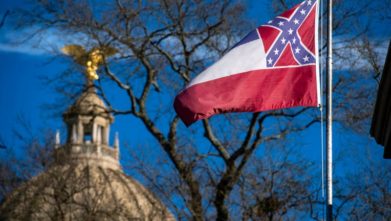 FILE - The Mississippi State Capitol dome is visible in the distance as the flag of the state of Mississippi flies nearby in Jackson, MS on January 10, 2019.