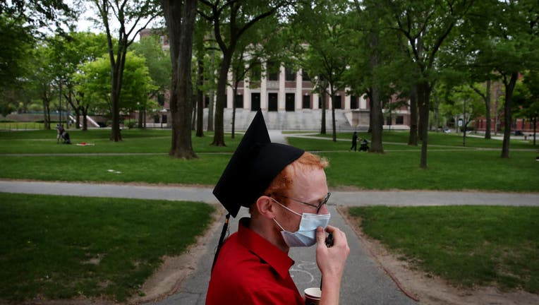 FILE - Harvard Law School graduate spends time on campus before attending the online graduation ceremony in his room.