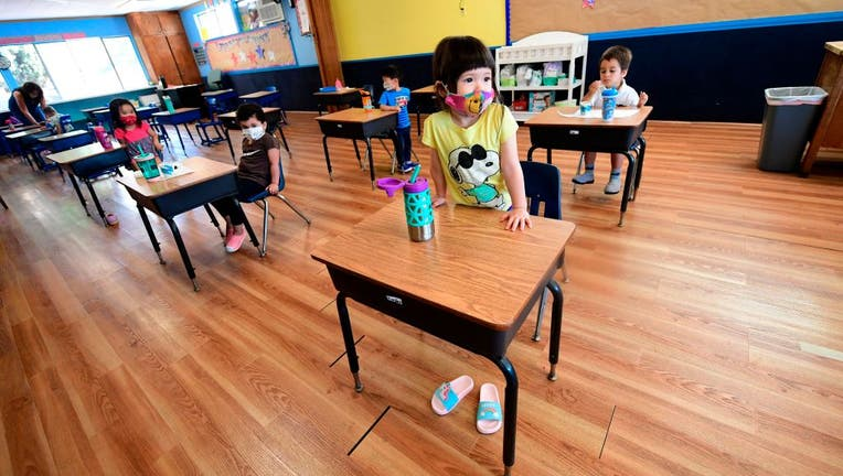 FILE - Children in a pre-school class wear masks and sit at desks spaced apart as per coronavirus guidelines during summer school sessions.