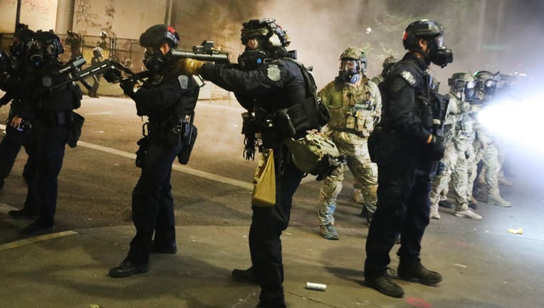 FILE - Federal police face off with protesters in front of the Mark O. Hatfield federal courthouse in downtown Portland as the city experiences another night of unrest.
