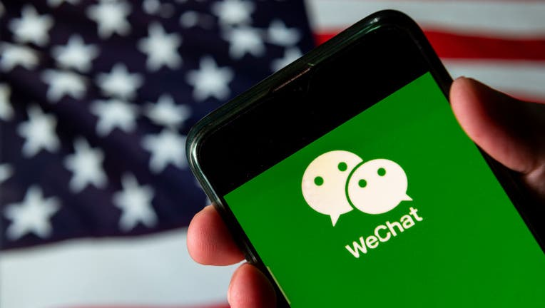 FILE - In this photo illustration the Chinese multi-purpose messaging social media and mobile payment app developed by Tencent, WeChat logo is seen on an Android mobile device with United States of America flag in the background.