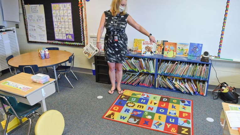 FILE - Shiloh Hills Elementary School principal Kelly Byrne shows in a 1st grade classroom how an area has been marked off for the teacher, to help remind them where they can stand to still maintain social distancing.