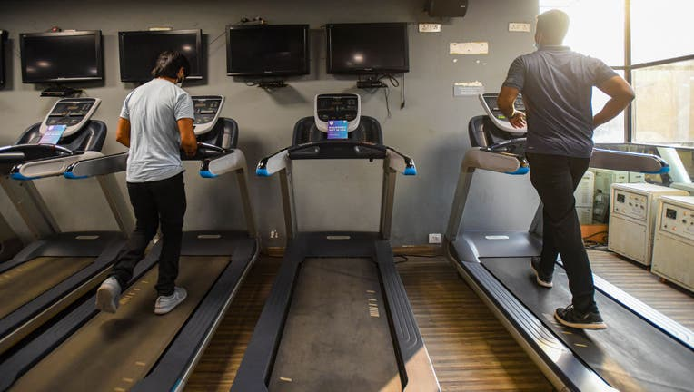 An image taken Sept. 14, 2020 shows two people running on treadmills inside a gym in New Delhi, India. (Photo by Amal KS/Hindustan Times via Getty Images