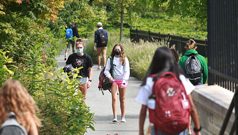 FILE - Students wearing masks walk around the Boston College Campus in Newton, MA on Sept. 14, 2020. There has been a coronavirus outbreak at the college.