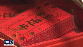 Firecrackers ward off evil spirits, signs of familiar Lunar New Year symbolism prevail