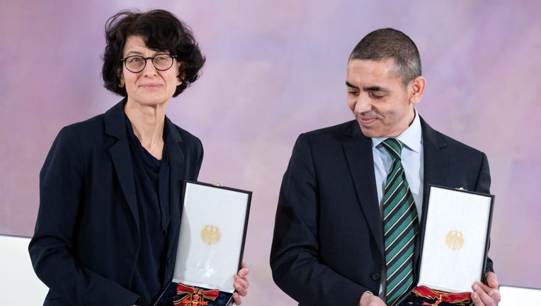 Özlem Türeci (L) and Ugur Sahin (r), founders of the coronavaccine developer BioNTech, stand during the award of the Grand Cross of Merit with Star of the Order of Merit of the Federal Republic of Germany on March 19, 2021 in Berlin, Germany. (Photo by Bernd von Jutrczenka/picture alliance via Getty Images)