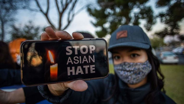 A woman holds her phone during a candlelight vigil in Garden Grove, California, on March 17, 2021 to unite against the recent spate of violence targeting Asians and to express grief and outrage over a shooting that left eight people dead in Atlanta, Georgia, including at least six Asian women. (Photo by APU GOMES/AFP via Getty Images)
