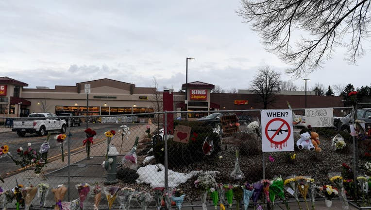 Flowers line an ever-growing memorial along the sidewalk and fence a day after a mass shooting at King Soopers, on March 23, 2021. (Photo by AAron Ontiveroz/MediaNews Group/The Denver Post via Getty Images)