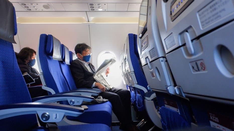 A passenger wearing a face mask seen reading a news paper