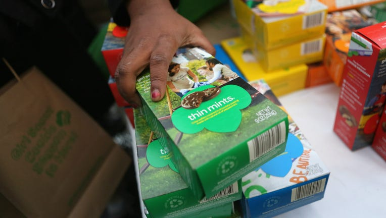 82632234-Girl Scouts sell cookies.