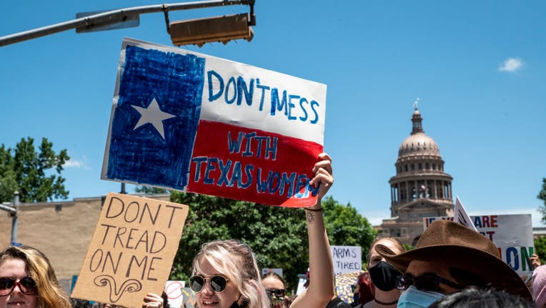 FILE: Protesters hold up signs as they march down Congress Ave at a protest outside the Texas state capitol on May 29, 2021, in Austin, Texas. (Photo by Sergio Flores/Getty Images)