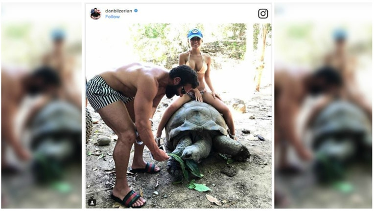 f7412566-Controversy over photo of bikini-clad woman on 100-year-old tortoise-404023