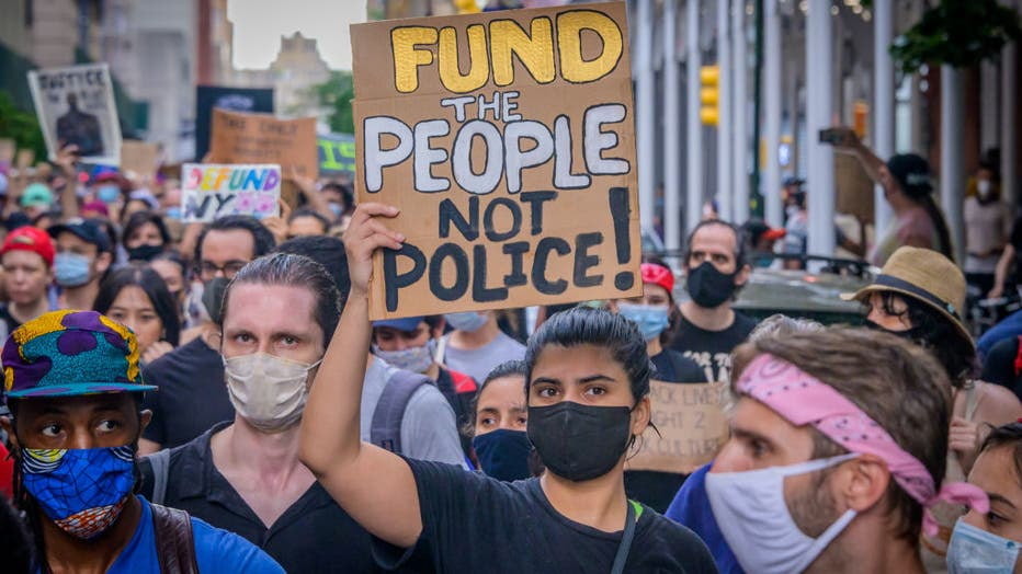 05b646b0-A participant holding a Defund Police sign at the protest.