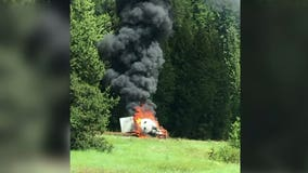 Truck driver rushed to hospital after semi crashes, catches fire on I-90