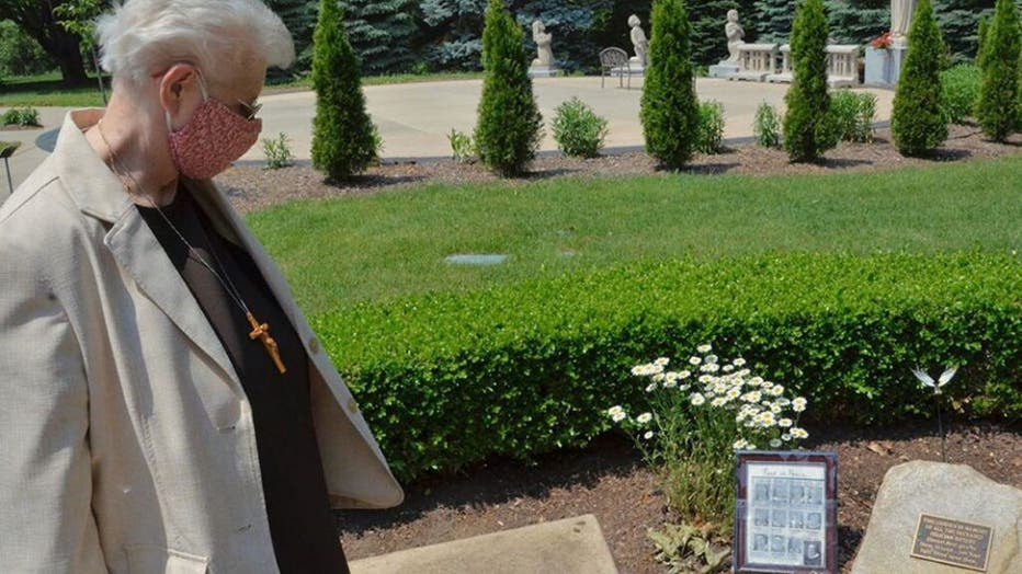 Local-minister-Sr.-Mary-Andrew-Budinski-looks-at-the-memorial-to-remember-the-12-sisters-who-died-in-one-month-from-COVID-19-that-sits-in-the-gardens-outside-the-Felician-Sisters-convent-in-Livonia-Michigan..jpg