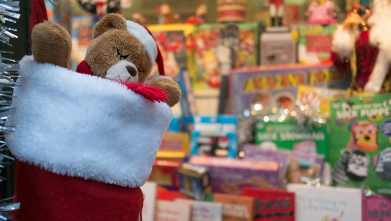 Teddy bear in stocking in front of Christmas gifts.