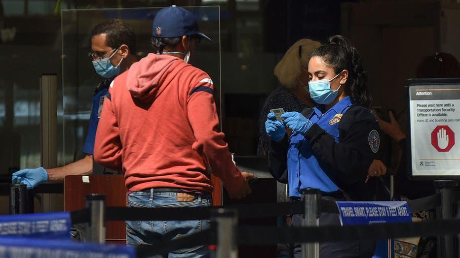 A TSA officer checks a man's ID at a screening checkpoint at