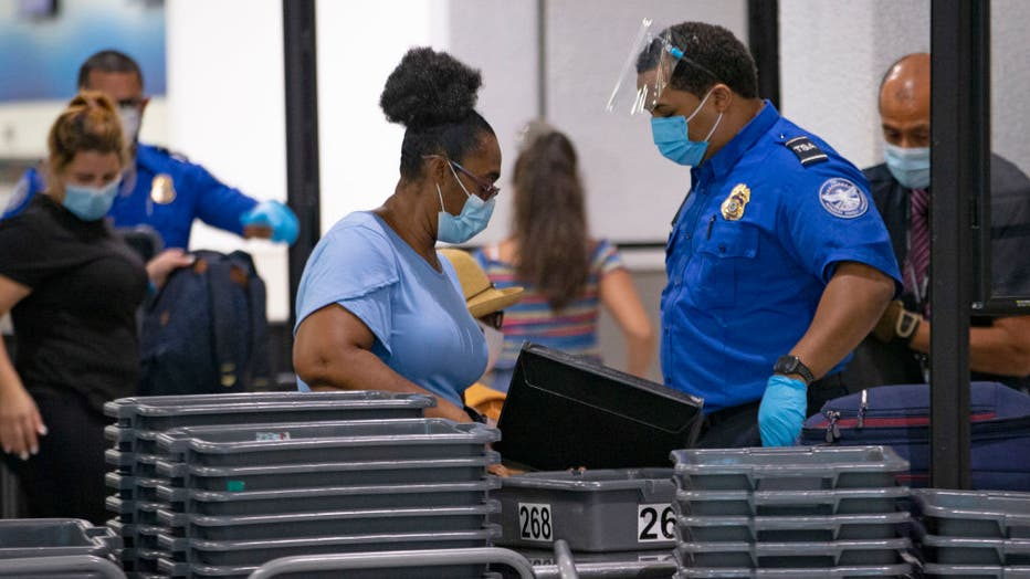 FILE - A TSA worker wears a mask while helping travelers get through a security checkpoint at the Miami International Airport on Nov. 22, 2020 in Miami, Florida. (David Santiago/Miami Herald/Tribune News Service via Getty Images)