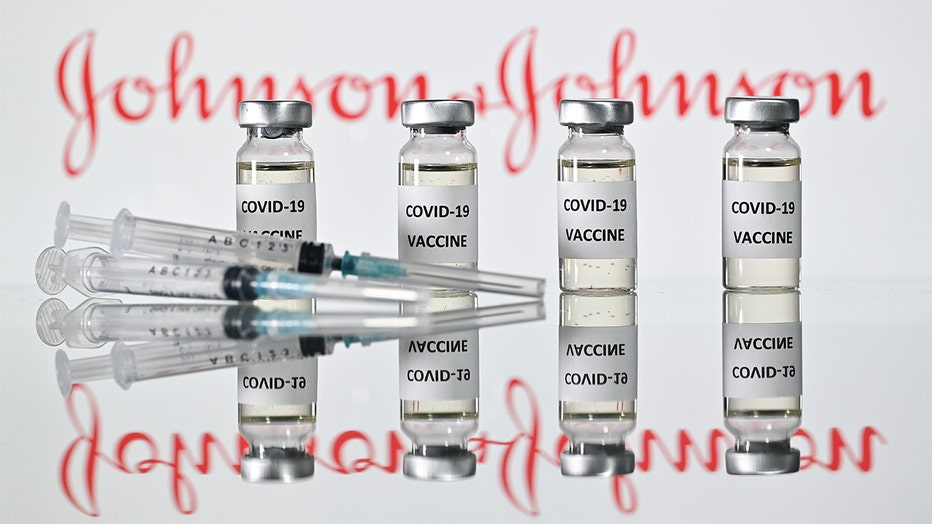 An illustration picture shows vials with Covid-19 Vaccine stickers attached and syringes with the logo of US pharmaceutical company Johnson & Johnson