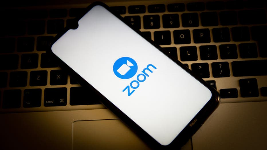 In this photo illustration, a Zoom logo seen displayed on a