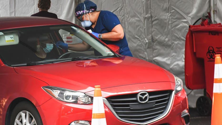 A man receives a nasal test at a drive-thru COVID-19 testing