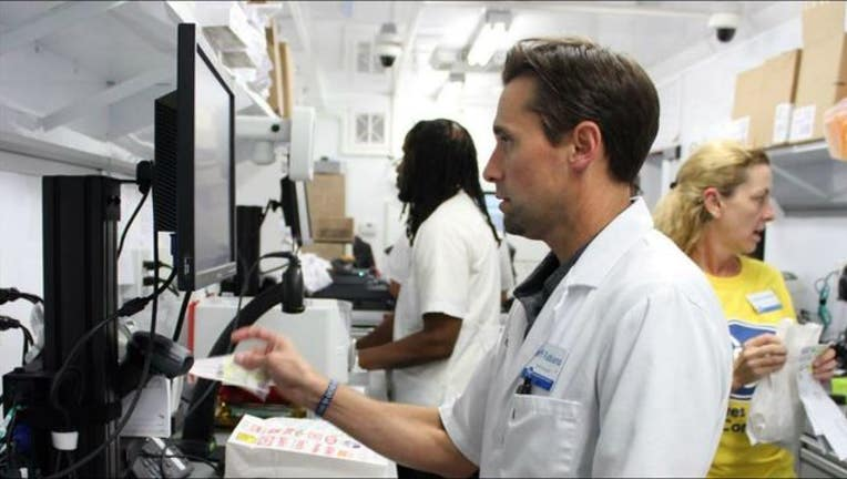 85fa80b3-Pharmacist Jeff Fabiano fills a prescription at a mobile pharmacy outside an evacuee shelter in Houston-404023