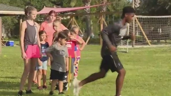 Young man helps other learn to play football