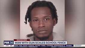 Man with gun scales school fence