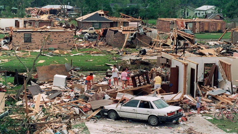 A group of people sift 28 August 1992 through the