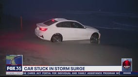 Car stuck in sand after rising tide