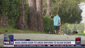 Man using sign to urge drivers to slow down